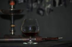 Een cognacglas op een grijze achtergrond, waterpijpbuis Royalty-vrije Stock Fotografie