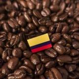 Een Columbiaanse die vlag over geroosterde koffiebonen wordt geplaatst royalty-vrije stock afbeelding