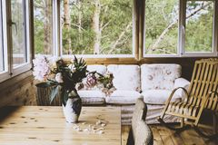 Een comfortabel terras met meubilair - een houten schommelstoel, een bank, pioenen in een vaas op de lijst en rieten stoelen met  stock afbeelding