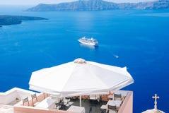 Een comfortabele koffie die het Egeïsche Overzees en een drijvende stoomboot op het Eiland Santorini overzien Toneel natuurlijk l stock foto