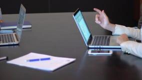 Een commerciële vergaderingshanden die laptop met stats met behulp van stock video