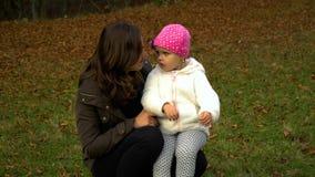 Een communiceren de jonge moederspelen met haar weinig dochter in het de herfst bosmamma en dochter Zij zijn gelukkig stock footage