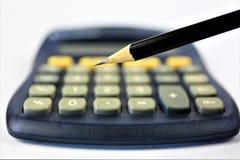 Een conceptenbeeld van een calculator met een potlood en exemplaarruimte stock fotografie