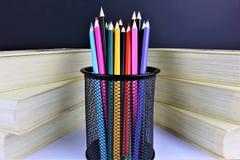 Een conceptenbeeld van sommige kleurrijke potloden met sommige boeken royalty-vrije stock afbeeldingen