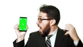 Een conceptueel model Gebaarde zakenman die met glazen een smartphone met het groen scherm houden stock footage