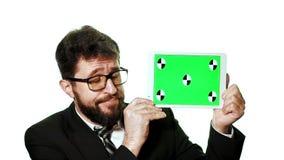 Een conceptueel model Gebaarde zakenman die met glazen een tablet met het groen scherm houden stock video