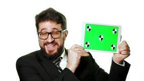 Een conceptueel model Gebaarde zakenman die met glazen een tablet met het groen scherm voor hem houden stock video