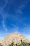 Een concreet gebouw, dat als de sferische oppervlakte van de maan kijkt neemt over de heldere blauwe hemel met wolken toe Stock Foto