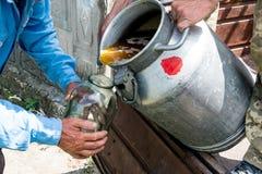 Een container met een zoete zoete honing Het werkimker Het helen van product van imkerij Mei, bloemhoning Stock Afbeelding