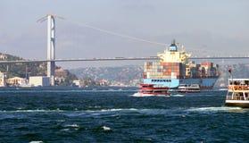 Een containerschip en verscheidene kleine passagiersschepen dichtbij 15 Juli martelen Brug op Bosphorus stock foto
