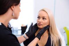 Een cosmetologist houdt handen en onderzoekt het gezicht van een vrouw alvorens procedures uit te voeren Het meisje bij de ontvan stock afbeelding