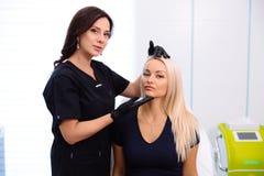 Een cosmetologist houdt handen en onderzoekt het gezicht van een vrouw alvorens procedures uit te voeren Het meisje bij de ontvan royalty-vrije stock fotografie