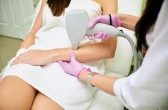 Een cosmetologist voert een procedure voor de verwijdering van het laserhaar van het lichaam van een meisje uit stock afbeelding