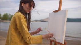 Een creatieve vrouwenkunstenaar bereidt een canvas met een grote borstel en een oplossing voor stock video