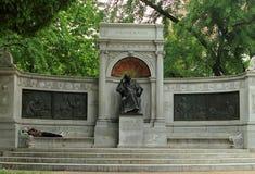 Een dakloze mens die een dutje op de bank van Samuel Hahnemann Monument nemen stock foto's