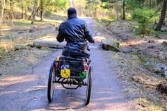 Een dakloze mens in een rolstoel berijdt op een bosweg De three-wheeled rolstoel is uitgerust met een doos voor dingen Silhouet stock afbeelding