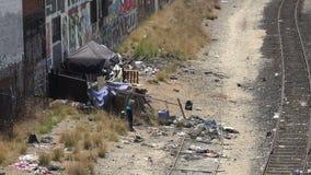 Een dakloze vrouw die door afval langs de spoorwegsporen doorzoeken stock footage