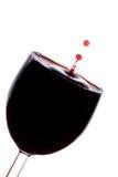 Een daling van rode wijn valt in het glas Stock Foto