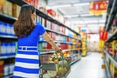Een dame die een boodschappenwagentje in wandelgalerij het winkelen duwen Stock Foto's