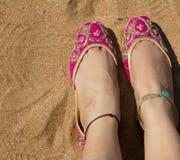 Een dame die een paar roze traditionele Indische jutis van vrouwen` s schoenen dragen bij het Anjuna-strand in Goa, India Stock Fotografie