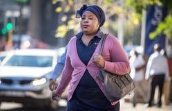 Een dame die onderaan weg in stad lopen stock fotografie