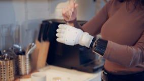 Een dame met een bionische hand voegt kruid in de kop toe stock videobeelden