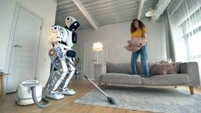 Een dame speelt met een hoofdkussen terwijl een cyborg schoonmaakt stock videobeelden