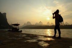 Een damefotograaf die de zonstijging vangen Stock Afbeelding