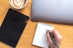 Een de holdingspotlood van de vrouwen` s hand aan het schrijven op leeg notitieboekje met tablet, laptop en koffie op houten lijs Stock Fotografie