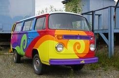 Een de kampeerautobestelwagen uitstekende die van Volkswagen (VW) met psychedelische hippy kleuren wordt geschilderd Stock Fotografie