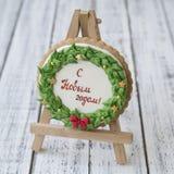Een de peperkoekkoekje van glanskerstmis in de vorm van een Kerstmiskroon met een rode boog en gouden sterren met inschrijving in royalty-vrije stock foto