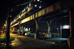 Een de stadsmetro die van Chicago CTA over een brug in een donkere ur gaan Stock Afbeeldingen