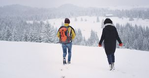 In een een de toeristenman en vrouw die van de winterdag twee door het sneeuw bevroren gebied lopen, gaan zij naar hun bestemming stock footage