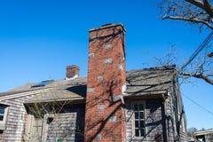 Een deel van betegeld dak met baksteenschoorsteen tegen wolken Stock Foto's