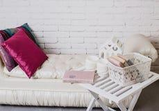 Een deel van binnenland met laag en decoratieve hoofdkussens, witte houten lijst met boeken op het Royalty-vrije Stock Foto