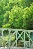 Een deel van brug in staalstructuur en groen rond Stock Foto