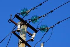 Een deel van een concrete pijler met draden tegen een blauwe hemel stock fotografie