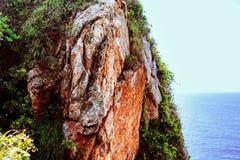 Een deel van de rotsachtige bergen in het gras op waterachtergrond Stock Fotografie