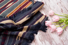 Een deel van de sjaal in strepen en ornament, roze tulpen Lichte houten achtergrond Stock Afbeelding