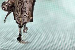 Een deel van een oude naaimachine met een poot, naald, draad, en een stuk van gekleurde stof Achtergrond voor uw ontwerp Scherpte Royalty-vrije Stock Foto's