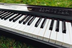 Een deel van elektrisch pianotoetsenbord, groene grasachtergrond Stock Afbeeldingen