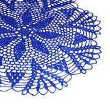 Een deel van geïsoleerde gehaakte heldere blauwe doily met een patroon van bloem op een witte achtergrond Ronde decoratieve katoe stock afbeeldingen