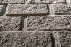Een deel van grijze concrete muur met metselwerkimitatie Stock Foto