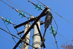 Een deel van een grijze concrete pijler met elektrodraden en een lamp tegen de blauwe hemel royalty-vrije stock foto