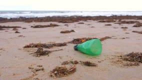 Een deel van groene plastic fles werd gebracht aan de kust op de zandige kust stock footage
