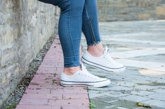 Een deel van het lichaam Benen van een jong meisje in blauwe denimbroek en witte tennisschoenen stock foto