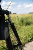 Een deel van het voorwiel met resors tegen de achtergrond van het gebied van de de lente groene rogge en de rode papavers stock foto's