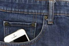 Een deel van mobiele witte cellphone in de voorzak blauw denim Royalty-vrije Stock Foto's