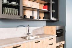 een deel van moderne schone lichte keuken met gootsteenkraan en planken royalty-vrije stock foto's