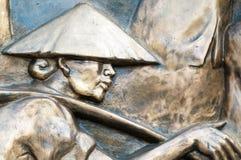 Een deel van monument met de mens in hoed in Vietnam, Azië. Stock Foto